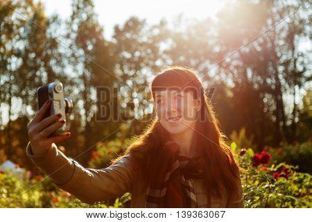 Lovely brunette girl doing selfie in a beautiful garden, backlit