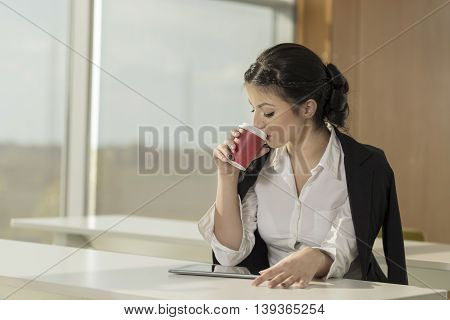 Young business woman sitting at her desk in an office working and drinking coffee