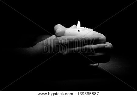 Praying Hands with light candle in dark background black and white