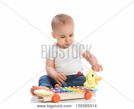 Baby playing percussion isolated on white, close up