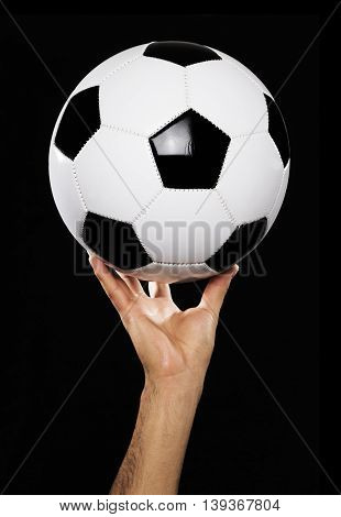 Man hand with new Black and white soccer ball on white background.