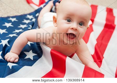 adorable baby girl lying on american flag background
