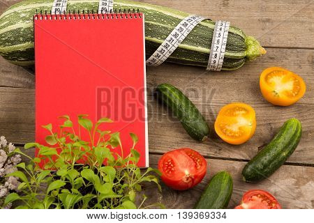 Marrow Squash, Measure Tape, Blank Red Notepad, Flowers, Tomatoes And Cucumbers On Brown Wooden Tabl