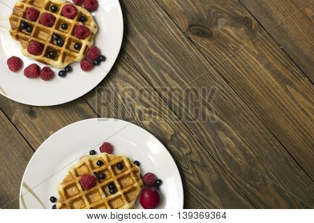 Two white plates with waffles , they raspberries and blueberries top view
