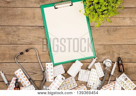 Pills, Medical Bottle, Syringe, Stethoscope And Blank Clipboard On Brown Wooden Table