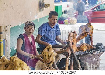 AZUAY, ECUADOR, OCTOBER - 2015 - Couple of chefs cooking traditional roasted cuy at street market in Azuay province Ecuador.