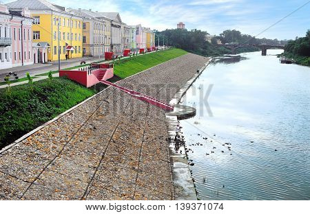 Scenic view of embankment in old part of city at summer. Ancient buildings bridge over river. Cityscape
