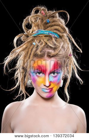 Portrait of young blonde with colorful face and dreadlocks. Isolated on black