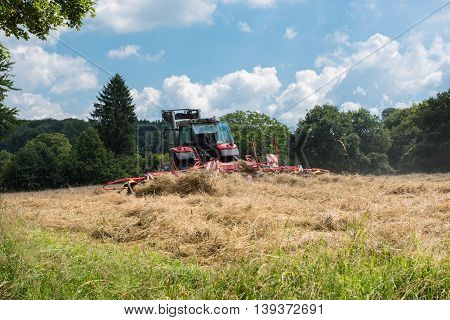 tractor with tedder turning hay on the meadow