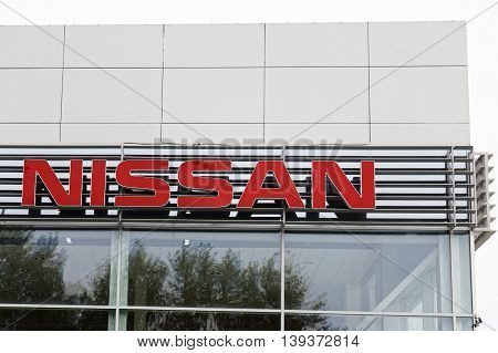 A Nissan Sign On The Building Car Selling And Service Center.