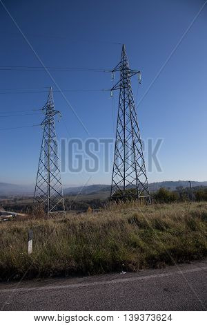 Two pylons of high voltage seen from below on a clear sky background