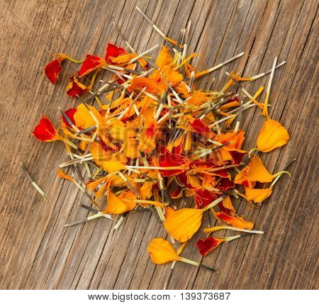 a handful of marigold petals scattered on the old board in the cracks. top view close-up