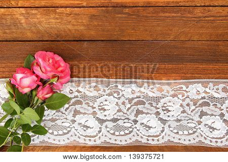 beautiful flowers roses on a wooden background with lace