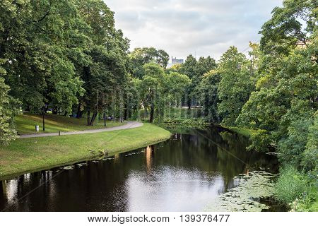 Summer city park with river in historic center of Riga Latvia