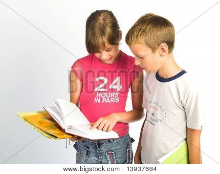 Young girl and boy reading book .