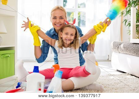 Mother and kid cleaning room together at home