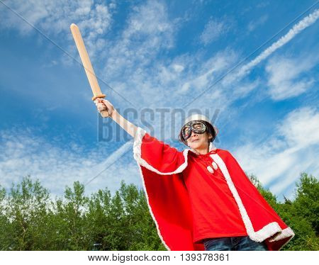 Low angle view of cute teenage boy wearing metal colander as a helmet goggles and red costume holding wooden sword pretending to be a power super hero