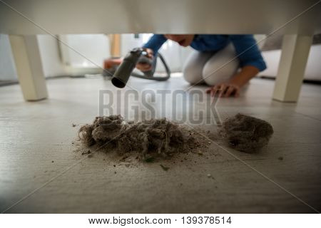 Housewife Using Vacuum Cleaner For Dust At Home