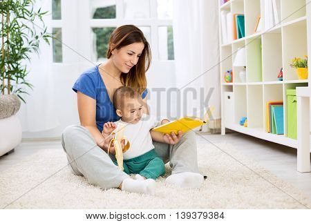 Young Mother Telling A Story To Her Baby And Giving Banana For Snack