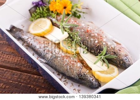 Trouts In Blue Ceramic Pan With Butter And Lemon