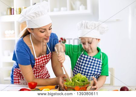 Mother and son prepare lettuce together in the kitchen
