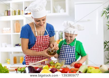 Mother And Child Putting Olive Oil To Vegetables Lettuce