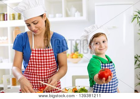 Mother Cooking Lunch And Little Cute Boy Holding Tomato
