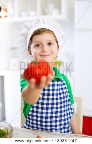 Little cute child boy with cook hat holding tomato in kitchen