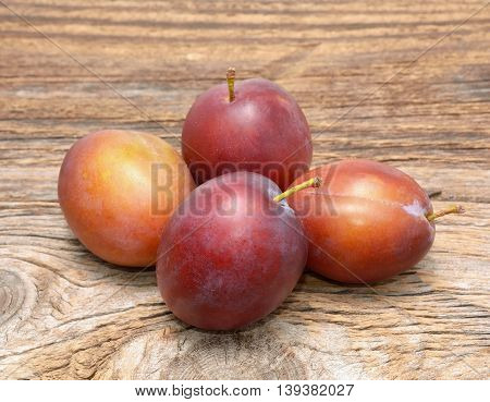 plums isolated on wooden background in studio