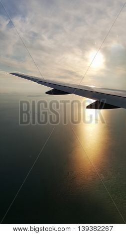 Wing of plane on beautiful sunset and sunrays and clouds view from window of the airplane