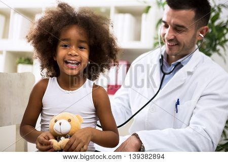 Pediatrician doctor examining happy smiling kid at hospital