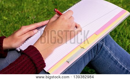 girl sitting on green grass and holding a notebook on her lap, the hand writes a red pen, burgundy sweater and jeans