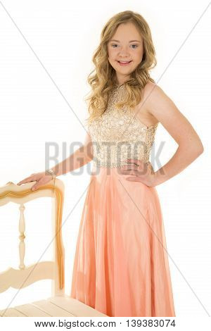A woman who has down syndrome in her peach dress standing by a bench with a smile.