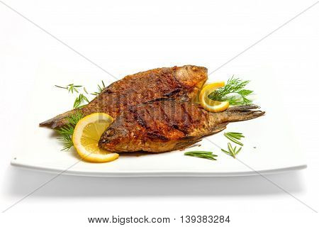 two fried carp with lemon and dill on a white plate