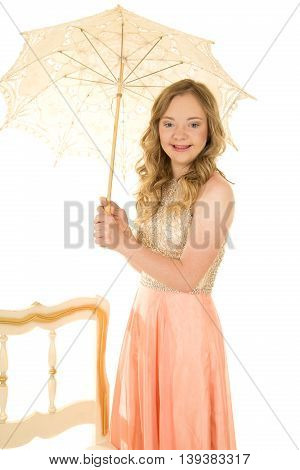 A woman with down syndrome in her peach dress smiling and holding on to a vintage umbrella.