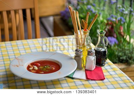 Italian serving of gaspacho. Table set with Italian spirit