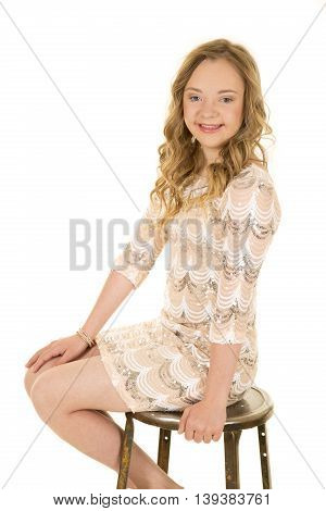 A woman with down syndrome with a smile on her face sitting on a stool.