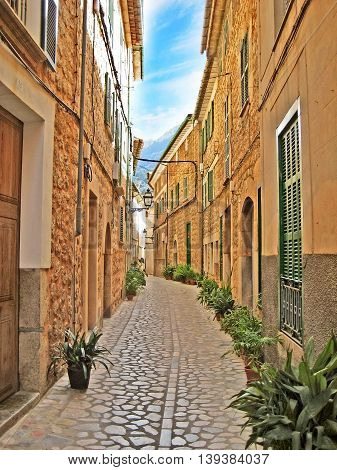 Cobblestone alley in Valldemossa Majorca - between narrow houses - view towards mountains of the Serra de Tramuntana