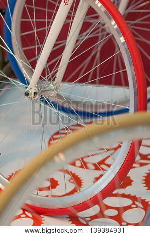 Closeup View Of Bike Red Wheel. Detail With Red Bike Wheel, Yellow Wheel And Blue Wheel..