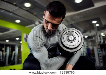 Strong powerful male exercise biceps with weight, healthcare concept