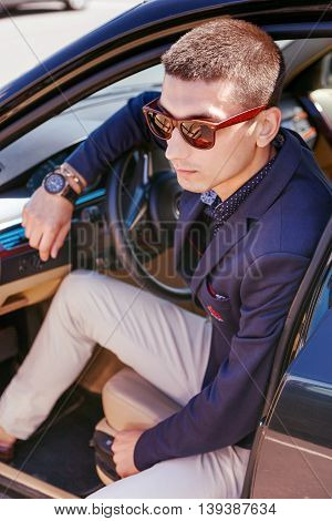 Young fashionable dressed businessman sitting in his car with one foot in the cabin.