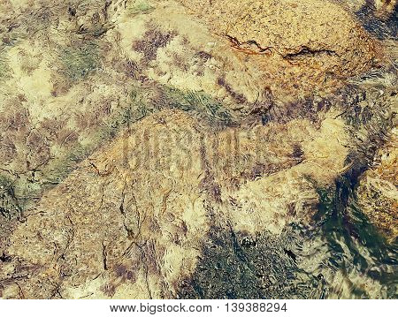 Golden underwater texture with the light on a rocky seafloor with stone pieces and moss