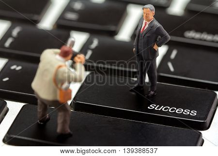 Miniature figurines of successful business with photographer on keyboard