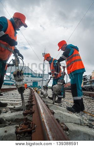 Tobolsk, Russia - July 15. 2016: Sibur company. Denisovka railway station. Railway workers repairing rail in rainy weather