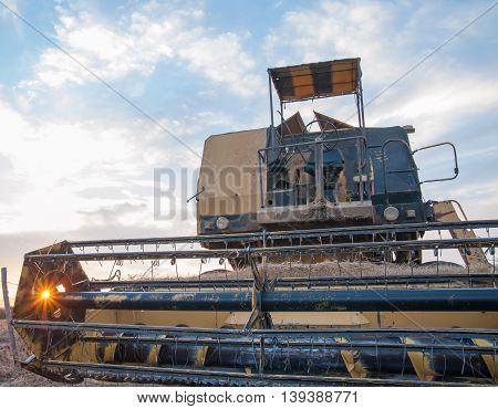 Closeup view of of a combine machine while sun setting through the reel