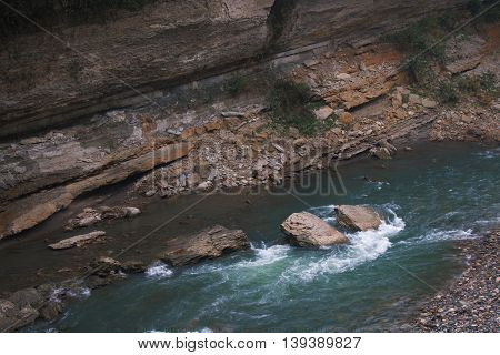 Landscape of rapid mountain river with cracked stone in canyon