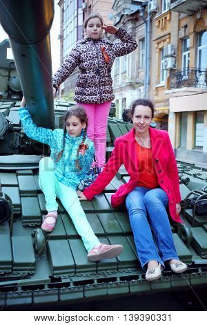 Woman and two girls pose on big armored tank in Samara during military parade, Russia
