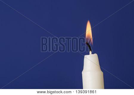 white burning candle on dark blue background