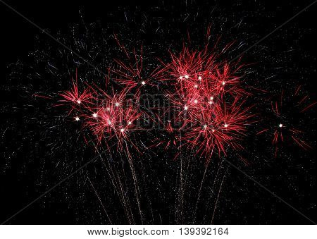 Red fireworks explode during 4th of July Holiday celebration