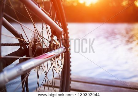 Bike stands on the dock near the river during sunset.